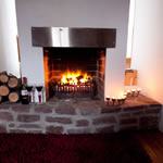Stone hearth and open fire at Achill Cottages