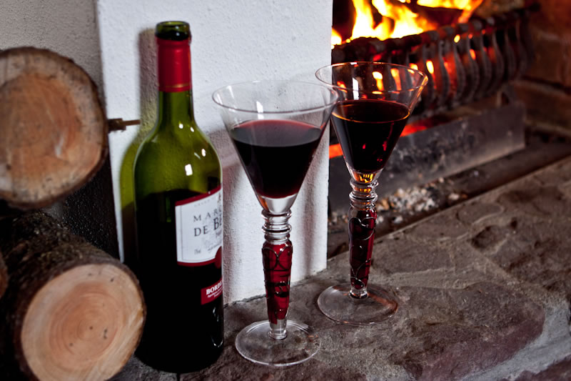 Open turf fire and hearthside with bottle of red wine and two glasses